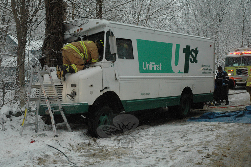 Richard Conrod, a volunteer firefighter and emergency medical technician for the Sandy Hook Volunteer Fire & Rescue Company, kneels on the hood of a van to aid the entrapped driver of the vehicle which had driven head-on into a tree on a snowy and icy Toddy Hill Road during a snowstorm during the morning of February 16. Other emergency volunteers were inside the van at the time aiding the injured driver, Carl Tomlin, 23, of Bridgeport.  (Gorosko photo)