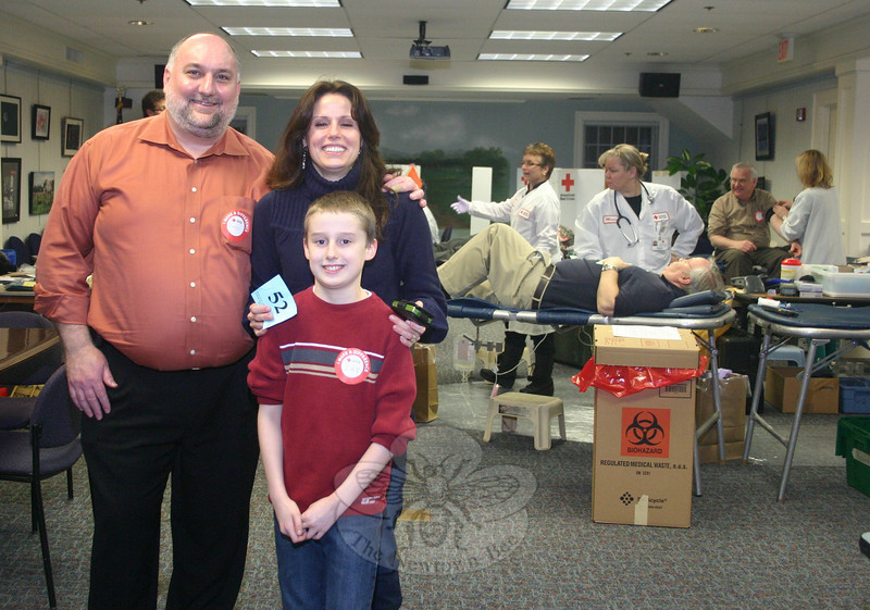 "Ian Wright, standing with parents Charles and Michelle, was the driving force behind an American Red Cross blood drive held in the lower meeting room of C.H. Booth Library on Wednesday, February 26. It was Ian's idea to do a blood drive while learning about community service as part of his fourth grade social studies curriculum. A change of location from The Alexandria Room at Edmond Town Hall to the library meant that only four tables were set up for donors instead of the originally planned for six tables, but the drive was nevertheless a success. It resulted in 49 viable donations, which will impact at least 147 lives. ""Newtown has such a great, giving spirit,"" said Lynne Phillips, account manager, biomedical services for the American Red Cross in Norwalk, who was checking donors in on Wednesday. ""We can't schedule enough drives for the donors who are always willing to help here.""  (Hicks photo)"