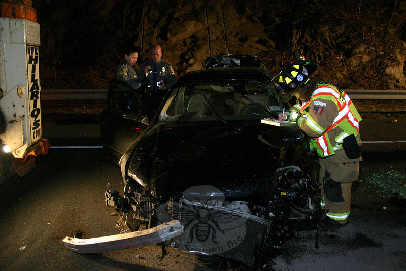 As state police look on, Sandy Hook Fire & Rescue EMS Captain Karin Halstead collects information on the hood of a crumpled auto that was involved in a one-vehicle rollover accident about 7:01 pm March 9 on westbound Interstate 84, just east of the Exit 11 off-ramp. State police said motorist Eric Oliver, 57, of Mahopac, N.Y., was driving a 2008 Audi A-4 sedan westward when the vehicle went off the pavement and entered the turf area off the right road shoulder. The sedan flipped over several times before it came to rest on its roof. Oliver, who was wearing a lap-shoulder safety belt when the crash occured, was able to get out of the auto by himself. The vehicle's airbags deployed. Newtown Volunteer Ambulance Corps members transported Oliver to Danbury Hospital for a medical evaluation. He was treated and released, a hospital spokeswoman said. Sandy Hook firefighters responded to the accident. State police verbally warned Oliver for failure to drive in the proper lane.  (Hicks photo)