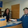 Former Newtown first selectman Joe Borst hands over one of the first letters to cross the counter to Hawleyville Post Office clerk Laura Smolen on Monday morning, shortly after the post office reopened in its new location. Mr Borst supported the efforts of the Save Hawleyville Post Office committee while he was in office.  (Crevier photo)
