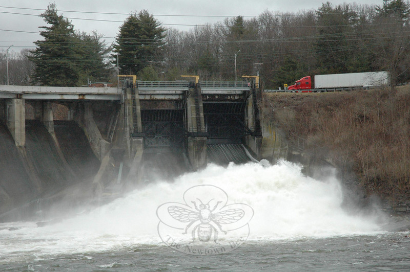 The heavy rains that came during the storm on the weekend of March 13-14 brought the Housatonic River at Stevenson Dam to flood stage. A tractor-trailer truck is shown approaching the road atop the dam that links Oxford to Monroe, as the river pours through the floodgates on the east side of the dam on Monday afternoon.  (Gorosko photo)