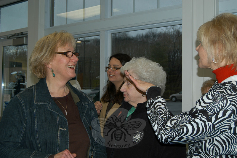 Terry Laslo, left, shares a laugh with her Save Hawleyville Post Office cohort Ann Marie Mitchell, as they celebrate the reopening of the historic post office. Stephanie Podewell and Terry Curry are in the background.  (Crevier photo)