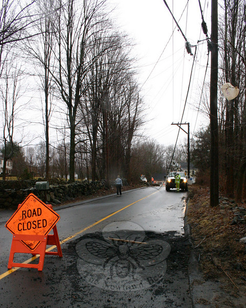 When a large tree near the end of the driveway at 40 Bennett's Bridge Road fell around 5:30 Saturday afternoon, it pulled down a live power line that burned for nearly an hour, creating a crevice that was the full width of one of the road's lanes. By Sunday morning when this photo was taken and an AT&T crew was making repairs to its lines, the damage to the roadway was clearly visible.  (Hicks photo)