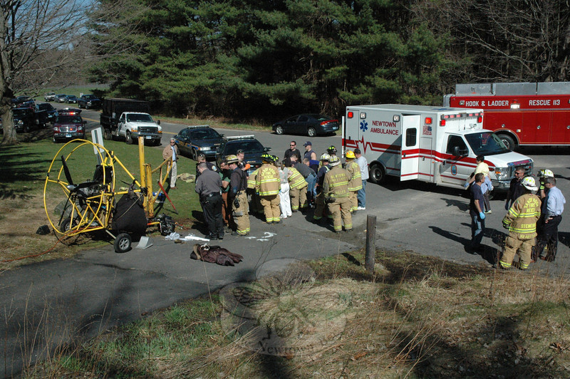 Emergency service personnel move an injured woman to an ambulance from the site of a collision where the powered-parachute aircraft that she was taxiing down a paved slope collided with a metal gate near the turnaround circle on Keating Farms Avenue at Fairfield Hills on Good Friday, April 2.  (Gorosko photo)