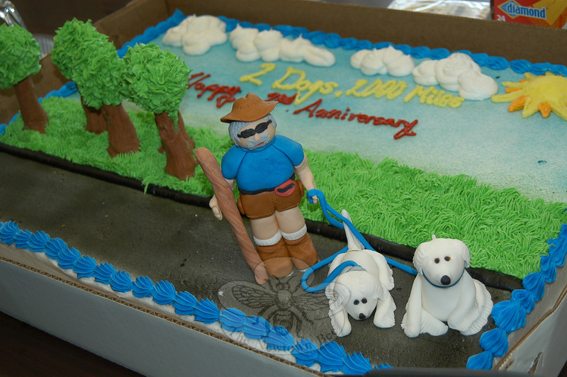 "A clever cake from Caraluzzi's Market in Newtown depicts Luke Robinson and his two Great Pyrenees, the ""2 Dogs, 2000 Miles"" trio who were in Newtown for the second time to promote awareness of comparative oncology. Mr Robinson and his dogs are walking from Austin to Boston.  (Crevier photo)"