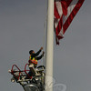 Newtown Hook & Ladder lowered the flag on Newtown's flagpole at 9:30 on April 5 in honor Marine Lance Corporal Tyler Griffin, 19, of Voluntown, who was killed recently while on active duty in Afghanistan. Mike McCarthy and Chris Proulx (hidden) climbed the fire company's ladder to lower the flag.  (Hicks photo)