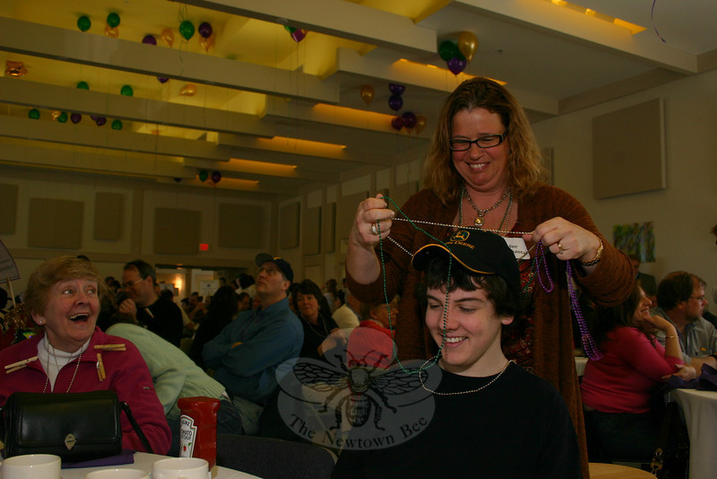 Sue Mouchantat, one of the co-chairs of the NEWS Advisory Board, had fun handing out Mardi Gras beads.  (Hicks photo)