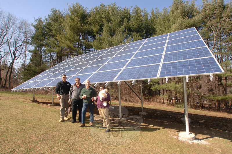 Resident Peter Alagna (second from right) celebrates as his new solar panels, behind him, that began to gather and generate power for his Head of Meadow home this month. He and his wife Rosalia, right, celebrate with Trinity Solar installer Mike Mazzamurro, far left, and consultant Bill Nastri.  (Bobowick photo)