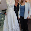 Julie Allen Bridals shop owner Melanie Mattegat, center, and daughter Lauren pose with the gown that gave them national attention this year. The gown was modeled in nationally televised advertisements for Ethan Allen Furniture after an Ethan Allen representative spotted it on the rack in the store last year, and was sought by brides who saw the furniture ad.  (Crevier photo)