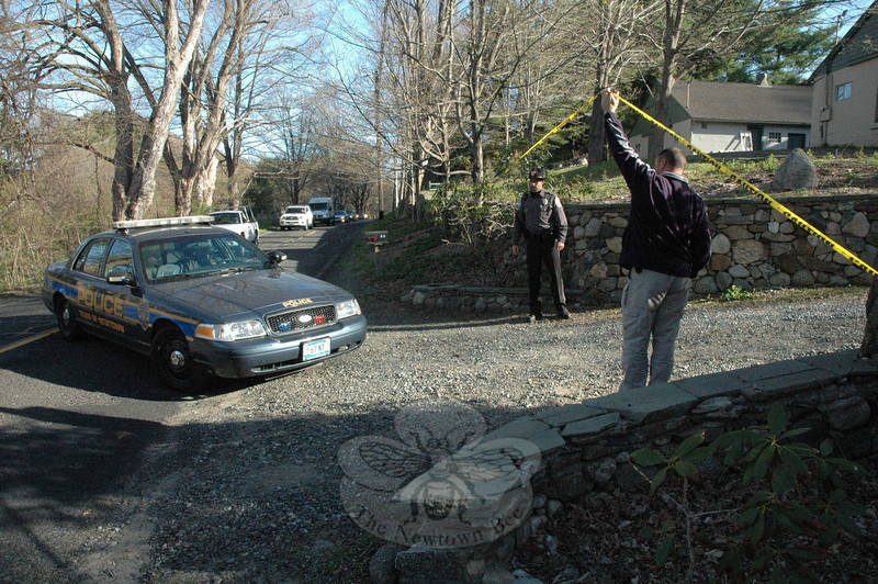 Crime scene tape is lifted to allow access for a Newtown police cruiser entering the driveway at 89 Poverty Hollow Road.  (Gorosko photo)