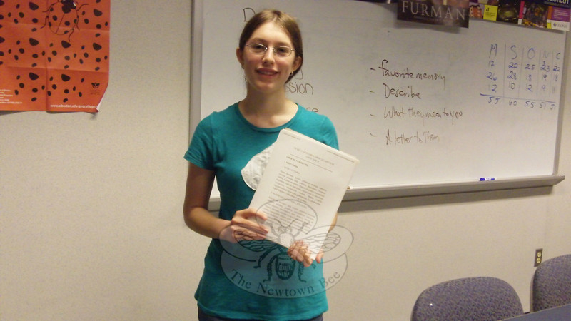 Eliana Kohrman-Glaser stands with a copy of the recipes she has been working to translate from Latin to English for her Junior/Senior Project at Newtown High School. Once finished translating, Eliana will work to rewrite the recipes to work as modern recipes.  (Hallabeck photo)