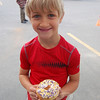 Aiden Kasbarian earned the first donut from Andrea's Pastry Shop at the third Annual Donut Dash on Sunday, April 11, after completing ten push-ups and raising money to go to Newtown Youth & Family Services.  (Hallabeck photo)