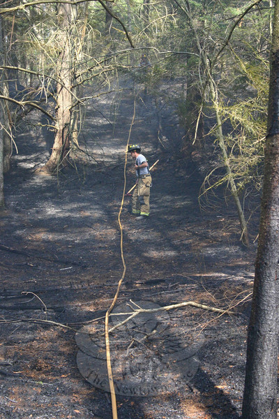 A firefighter follows a hose line that had been stretched up a hill from Miya Lane to Narragansett Train in Sandy Hook. Newtown's fire companies were kept busy with three brush fires during a four-day span earlier this week.  (Hicks photo)