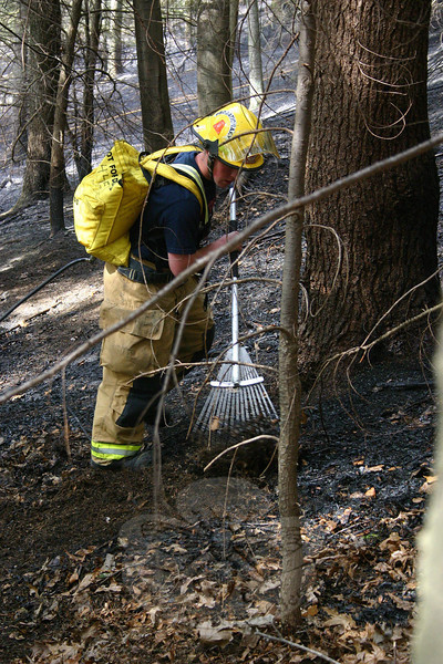 Sandy Hook Firefighter Liam Ferguson was armed with a water pack while using a rake to clear brush that was burned during a fire on April 11.  (Hicks photo)