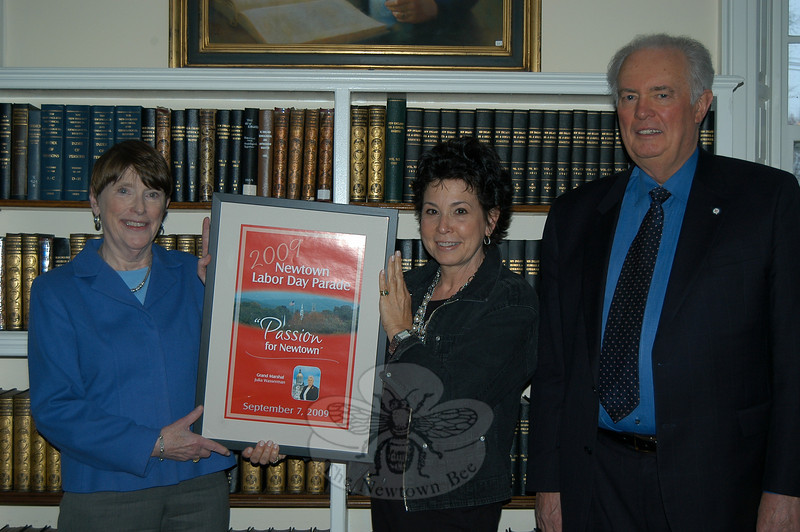 With thoughts turning to the Newtown Labor Day Parade, committee president Beth Caldwell, center, and parade committee treasurer Brian Amey, right, presented C.H. Booth Library director Janet Woycik with a framed copy of the 2009 Labor Day Parade program cover art on Tuesday, March 23. The parade committee has donated a framed cover poster to the library for several years. The 2009 picture will be on display near the main circulation desk of the library.  (Crevier photo)