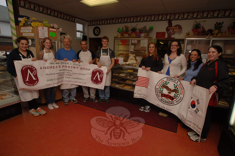 Holding the Andrea's Pastry Shop sign are staff, from left, Kat Altieri, Scarlet O'Sullivan, owner Tony Posca, John Posta, and on the right holding the ends of a second sign are Porco's Karate Academy representatives Lauren D'Amico and Amelia Shwartz, and from left in the center are Jessi Zeigler and Sheila Russo from Newtown Youth & Family Services.  (Bobowick photo)