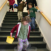 Children at Newtown Congregational Church enjoyed their annual Easter egg hunt last weekend, on Palm Sunday. Children were rounded up in the church's Great Room and then sent out, by age group, to the area where eggs had been hidden for them. Above, Leah Cribbin leads one group outdoors for their collecting time.  (Hicks photo)