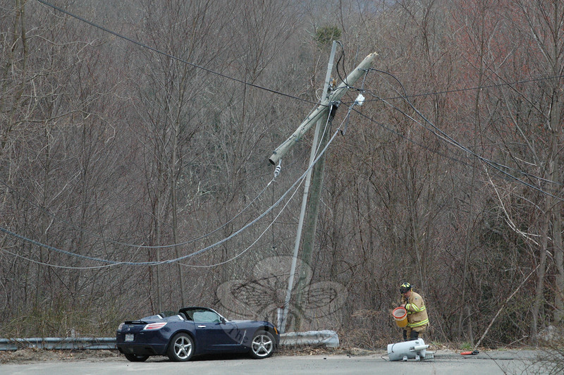 Sandy Hook Volunteer Fire & Rescue Company Firefighter Rob Sibley spreads some absorbent material to isolate spilled fluids near a fallen electrical transformer, which dropped from a utility pole at the end of the dead end Valley Field Road South, after the pole was struck by a motorist driving a sports car on the afternoon of March 25. Both the driver and a passenger escaped injury in the accident.  (Gorosko photo)