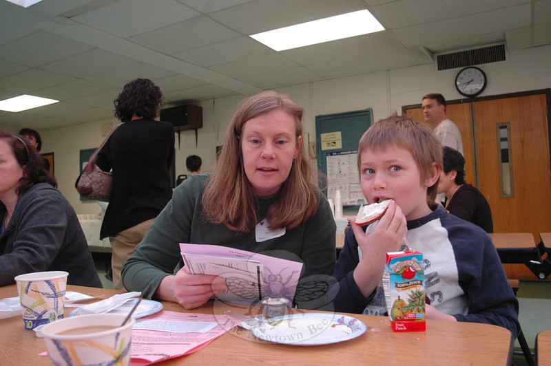 Newtown mom Pam Patterson reads over some of the Parent University materials before heading into her first workshop with her son, Dustin, 7, who was enjoying an early morning snack.  (Voket photo)