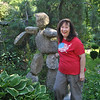 Rita Frost stands next to a stone figure crafted on site by Ethan Curry of Sticks and Stones Farm in Newtown. The figure is one of several large sculptures adding interest to her gardens.  (Crevier photo)