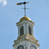 The bannerette-style weathervane on top of the Edmond Town Hall clock tower is embellished with sunbursts. The tail sunburst catches the wind, pointing the arrow to the direction from which the wind is coming, on this day, a little off of north. Bee Photo, Nancy K. Crevier