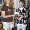 Flagpole Photographers member Sandy Schill, left, delivered a check for $350 from the photography group to C.H. Booth Library Director Janet Woycik on Monday, June 27. The money was raised through membership dues, according to Ms Schill.  (Hallabeck photo)