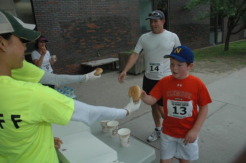 Steve Meeker and his son, Owen, received donuts at Newtown High School during the 4th Annual Donut Dash, a running event that was held June 25 to raise money for Newtown Youth & Family Services. The event is sponsored by Porco's Karate Academy.  (Gorosko photo)