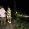 Sandy Hook Firefighter and MRT Richard Paloian checks driver Jon Petrovick, 27, of Brookfield, who was driving a 1995 Volkswagen Jetta sedan southward on Lakeview Terrace about 10 pm May 25, when he failed to follow a right curve in that road and then went off the pavement, coming to rest in a ditch, police report. Ambulance volunteers also checked and treated Petrovick at the scene. Sandy Hook firefighters went to the incident. Police verbally warned Petrovick for traveling too fast for conditions.  (Hicks photo)