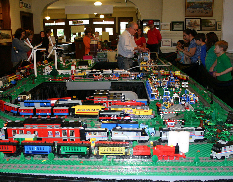 "The Danbury Railway Museum exhibition ""The Connecticut and Vermont LEGO® Railway,"" an operating model train layout made entirely of Legos, has been extended. Originally scheduled to close at the end of May, the exhibition will now remain on view until June 27. The popular traveling exhibit was created by Bill Probert (seen above, standing within the train layout, on May 23, answering questions for museum visitors), Elroy Davis and Steve Doerner, members of the New England Lego Users Group (NELUG). It features a half-dozen running trains, layouts of farm and soccer fields, buildings of many shapes and sizes, and even a trio of turbines. Museum admission is $7 for adults, $6 for seniors, and $5 for chil-dren ages 3-13; members and ages 3 and under are free. Museum hours are Wednesday through Saturday, 10 am to 4 pm; and Sundays, noon to 4 pm. The museum is in the restored 1903 Danbury Station and rail yard at 120 White Street in Danbury. For further information, call 203-778-8337, visit DanburyRail.org or send email to info@danburyrail.  (Hicks photo)"