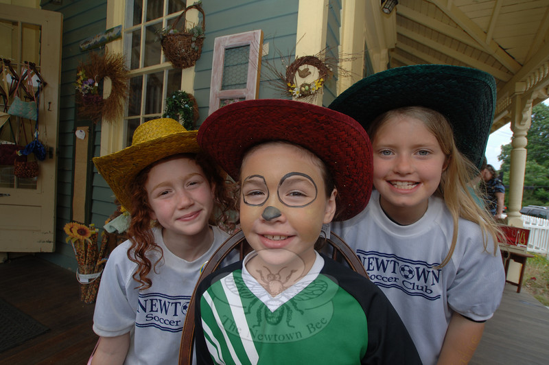 Sarah Widmann, left, and Katie Sailer, right, wait for a face painting like their friend Julie Raigosa. Sitting on the Wishing Well gift shop's porch, the girls waited their turn for Daniele Fredericks' Creative Face Art.  (Bobowick photo)