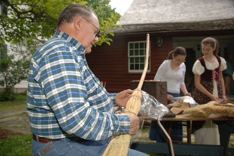 Emma Hungaski and Jenna Friedrich look at broom squire Bob Aborn's tools and handmade goods during Newtown Historical Society's open house and living history demonstration on May 16.  (Bobowick photo)