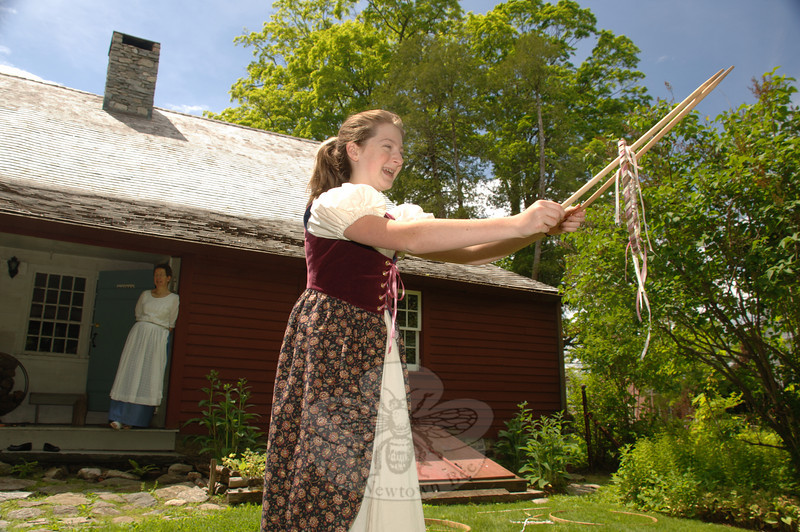 Jenna Friedrich played with old-fashioned toys, including the hoop she tossed from the end of her sticks, during Newtown Historical Society's open house on May 16. The game is played by tossing and catching the hoop with one or more other players.  (Bobowick photo)
