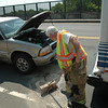 Sandy Hook Volunteer Fire & Rescue Company Firefighter George Lockwood, Jr, uses a broom to clean up some spilled automotive fluids following a two-vehicle accident that occurred about 11 am on May 26 on westbound Church Hill Road on the bridge above Interstate 84. The driver of a SUV was stopped and waiting behind a stopped compact Housatonic Area Regional Transit (HART) bus, which was waiting for a red traffic signal. When the signal turned green, the SUV rolled forward and struck the rear end of the bus. There were two passengers on the bus. There were no injuries, according to police.  (Gorosko photo)