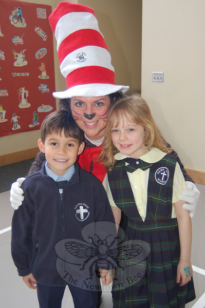 St Rose of Lima first grade teacher MaryJo Bokuniewicz dressed as Dr Seuss's The Cat In The Hat for March 2, Dr Seuss's birthday, recognized by the national Read Across America program. First graders Torin Kearney, right, and Erica Palmieri stand with their teacher at an assembly on Tuesday that had teachers reading other books by Dr Seuss to the students.  (Hallabeck photo)