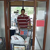 Newtown High School student Sakib Hossain rolls a donated shopping cart with food donations into the Newtown Food Pantry May 6. Besides the donations that were picked up by postal workers and volunteers around town last Saturday, others drove their donations directly to the Social Services office where they were whisked away for sorting by Sakib and other volunteers.  (Voket photo)