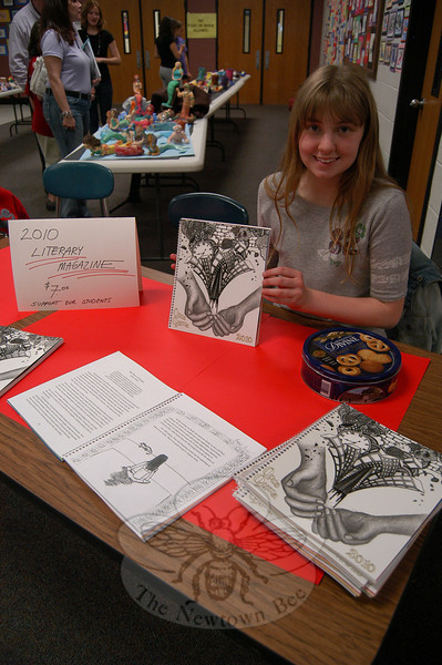 Newtown Middle School student Amy McGurk worked at a station during the NMS Celebration of the Arts on Tuesday, May 4, selling copies of this year's Literary Magazine. Amy said she has illustrations in the book on pages 32 and 34.  (Hallabeck photo)