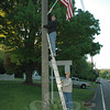 Four members of Newtown Lions Club were up early Monday morning, placing 30 flags in the brackets on telephone poles they put into place last year. Seen here are Vince LaSorsa, on the ladder, and Tom Evagash. The group started working around 6 am on May 10 and were finished with their task in less than an hour.  (R. Scudder Smith photo)