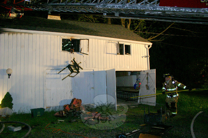 Sandy Hook Firefighter Rob Sibley clears debris away from the barn, while Hook & Ladder firefighters toss debris from the upper level of the building.  (hicks photo)