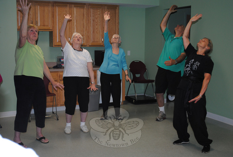 Tai chi instructor Dee Dee Calvey of New Milford (right) leads members of Newtown Senior Center through a series of exercises designed to improve breathing and balance. From left, June Summa, Bea Piskura, Virginia Cooney and John Bocuzzi follow Ms Calvey's lead. The class is a part of a ten-week session offered through a collaboration of Newtown Senior Center, Newtown Health District, and Newtown Visiting Nurse Association, with a goal of decreasing the likelihood of falls and injuries. The session includes a weekly tai chi class, balance assessment by a licensed physical therapist, an educational session with a pharmacist on how medications effect the risk of falls, and other fall-prevention techniques to use at home. Grant funding from the Connecticut Office of Rural Health makes it possible for the Newtown Health District to offer the program at no cost to the 16 participants who registered.  (Crevier photo)