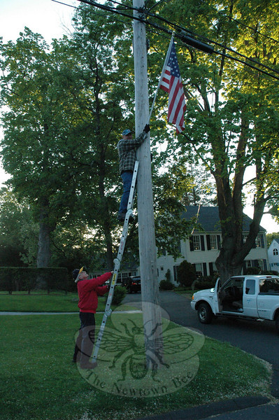 Four members of Newtown Lions Club were up early Monday morning, placing 30 flags in the brackets on telephone poles they put into place last year. Seen here are Paul Arneth, holding the ladder, and Wayland Johnson. This is the second year for the Lions Club flags, which line the east side of Main Street from Currituck Road to Glover Avenue. The club invested in three- by five-foot flags for the 2009 summer season, which debuted near the end of August and remained in place until early October. This year the flags are scheduled to remain in place until September 19. Because the flags didn't weather too badly last year, the Lions were able to use the same set this year. The Lions will return to Main Street this coming weekend, when they raise the large summer flag on the town's flagpole.  (R. Scudder Smith photo)