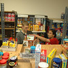Prabha Makayee and Travis LaBlanc shelve new donations of canned goods and nonperish-ables after they were sorted by volunteers who turned out Saturday, May 8, to support the annual US Postal Service food drive. The pair worked for several hours in the Newtown Food Pantry at Town Hall South.  (Voket photo)