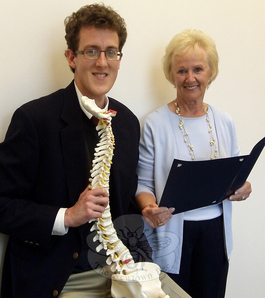 Local chiropractor Dr Aaron Coopersmith displays a spine model as First Selectman Pat Llodra presents a proclamation in recognition of National Correct Posture Month, which is celebrated during May.  (Voket photo)