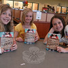 Reed Intermediate School fifth graders, from left, Sarah MacMullan, Calista Giroux, and Allie Indelicato hold their copies of Also Known As Harper, by Ann Haywood Leal, who spoke to students in the school's library on May 3.  (Hallabeck photo)
