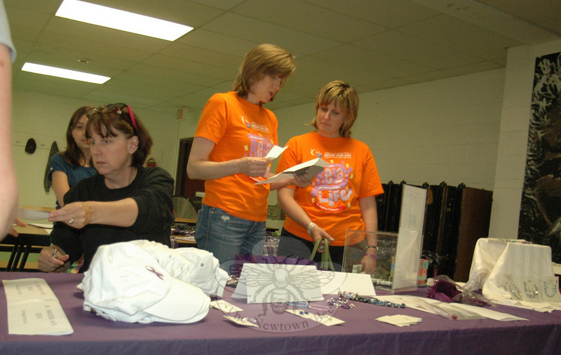 The final meeting of volunteers, organizers and team captains participating in the 2010 Newtown Relay For Life gathered May 6 in the middle school cafeteria to begin final preparations for the communitywide event, scheduled for June 5-6 at Fairfield Hills. Newtown's Relay webmaster Lynda Russo, standing at left, chats with Relay Chair Addie Sandler as an unidentified volunteer promotes a fundraising jewelry sale.  (Voket photo)