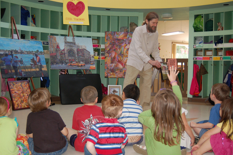 "Sandy Hook artist Glen River showed some of his paintings, including one depicting the former Red Brick General Store in Sandy Hook Center, an example of his ""Portraits of Places,"" with youngsters at the Children's Adventure Center on Friday, May 7.  (Crevier photo)"
