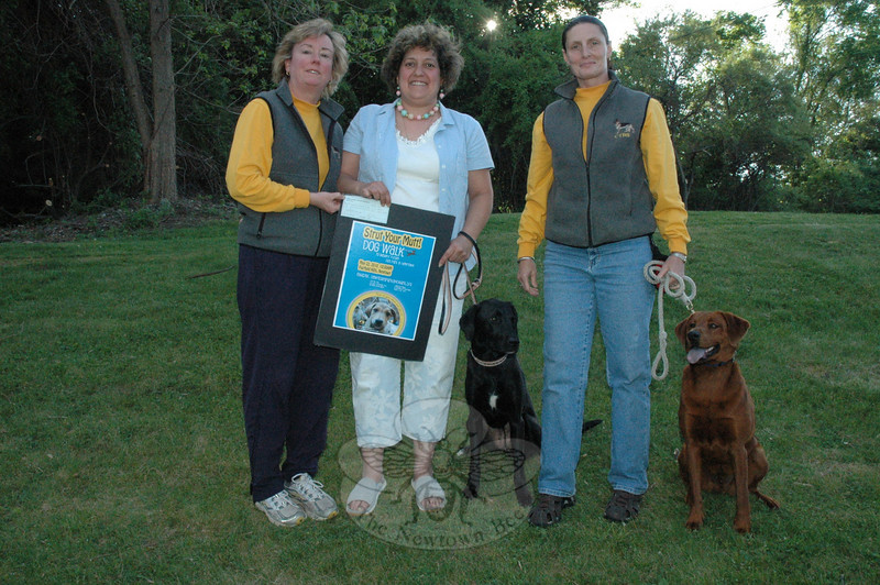 Dr Margaret Reed of Canine Training and Behavior Services, left, on May 6 presented a donation of $500 to RoseAnn Reggiano of the town's Parks & Recreation Department toward the creation of a fenced dog park at Fairfield Hills to be known as Newtown Park and Bark. Also present were dog trainer Patricia Fernandes and canines Cleo and Tucker. As a fundraiser for the dog park project, the department will hold an event known as Strut Your Mutt Dog Walk on Saturday, May 22, at Fairfield Hills. Information on the fundraiser is available at NewtownParkAndBark.org.  (Gorosko photo)