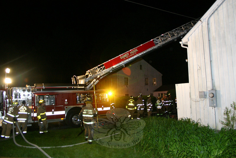 Sandy Hook Fire & Rescue used its ladder truck to get firefighters to the roof at 40A Chestnut Hill Road on Sunday night. The ladder truck also supplied water to the firefighters taking an aggressive interior attack against the fire.  (Hicks photo)