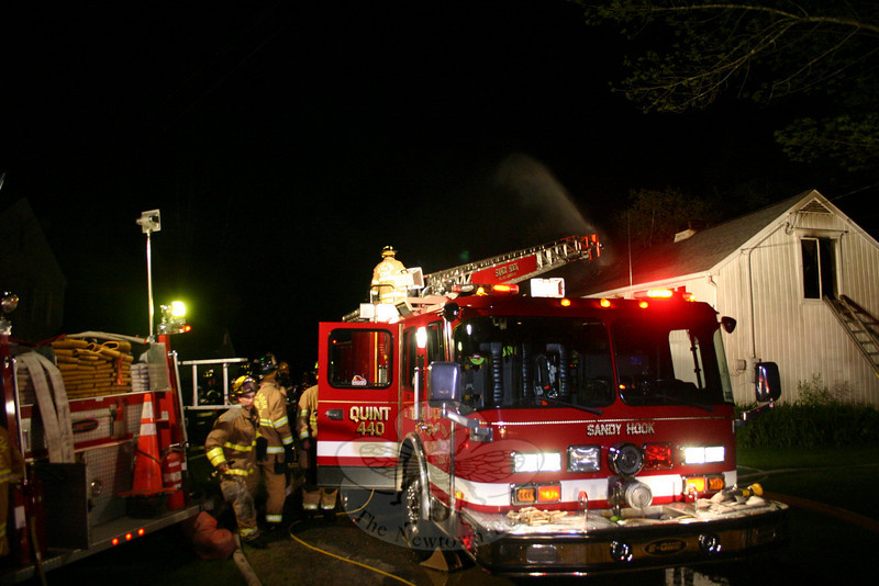 Sandy Hook Fire & Rescue used its ladder truck to get firefighters to the roof at 40A Chestnut Hill Road on Sunday night. The ladder truck also supplied water to the firefighters taking an aggressive interior attack against the fire. One spray of water can be seen coming from behind the barn in this photo. (Hicks photo)
