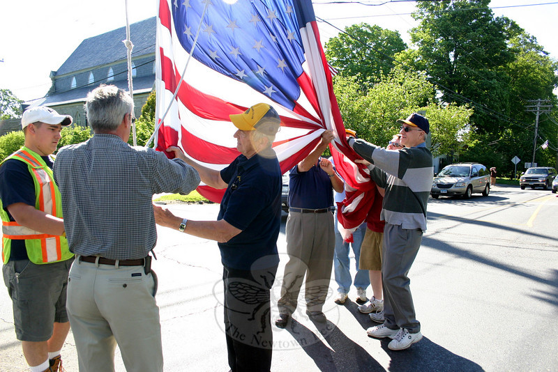 Tom Evagash holds the lower left corner of the winter flag while Dave Lydem disconnects it from the ropes on the Main Street flagpole Saturday, May 15. Mr Evagash and other members of the Lions Club, along with members of Newtown Hook & Ladder, were assisting Mr Lydem with the lowering of the old winter flag and the immediate raising of new 20 by 30 foot American flag for the summer.  (Hicks photo)