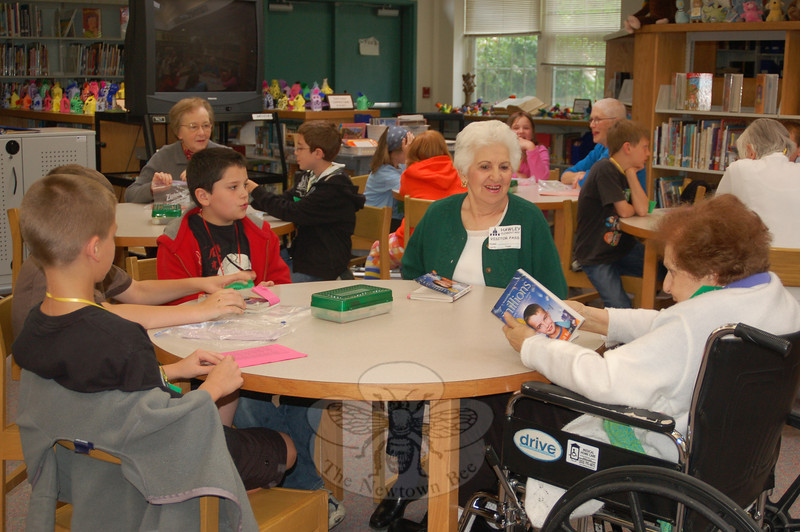 "From left, fourth grade students Tyler Rising, Jake Pirone, and Daniel Badiola discuss the book Millions with their senior buddies Connie Sciglimpaglia of Newtown and Dora Avallone of Brookfield. ""It's just wonderful,"" is Ms Sciglimpaglia's reaction to the donation of four Kindle e-readers to the group.  (Crevier photo)"